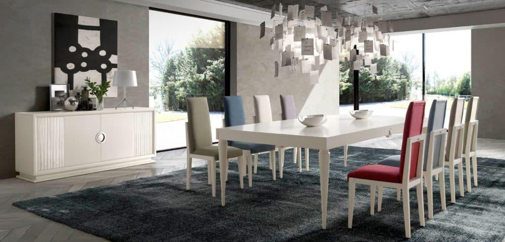 Mesa amplia y sillas con tapizados en varios colores, en tonos claros